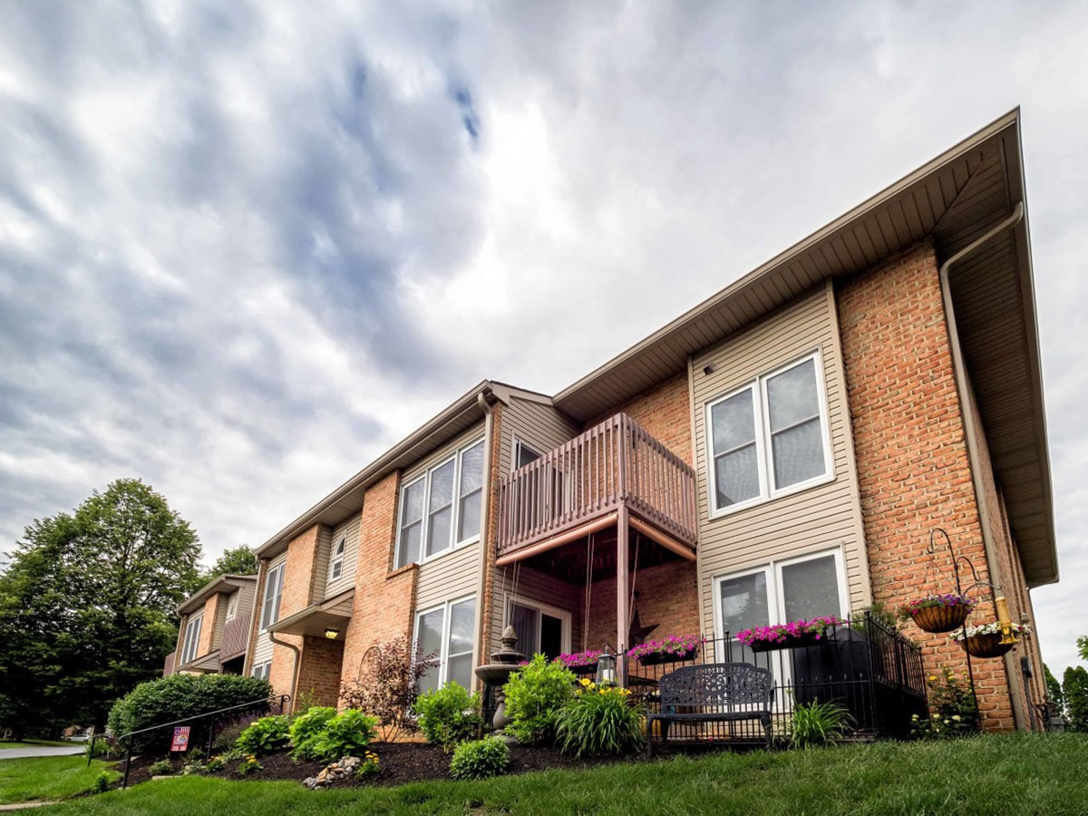 Exterior of Brookfield apartments for rent in Macungie, PA with beautiful front lawn and private balconies on sunny day