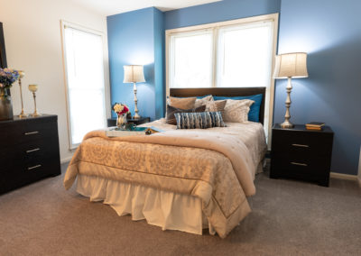 Spectacular model bedroom with carpeted flooring and two large windows in Brookfield apartments