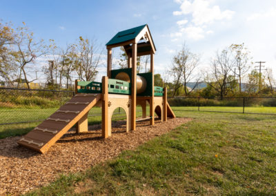 Child-friendly tot lot with expansive field for residents on Brookfield apartment grounds in Macungie
